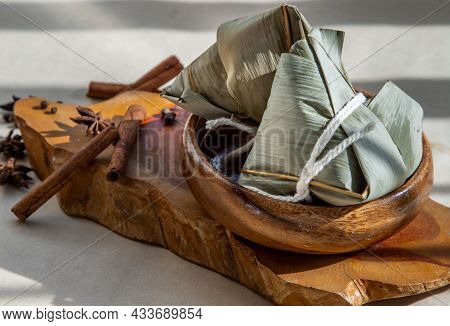 Chinese Rice Dumplings (zongzi) Shaped Pyramidal Wrapped By Leaves Ingredients On Wooden Plate. Famo