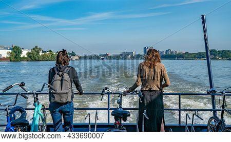 Rotterdam Netherlands - August 22 2021; Passenger Ferry Crossing Rotterdam Harbor With Two Women Sta