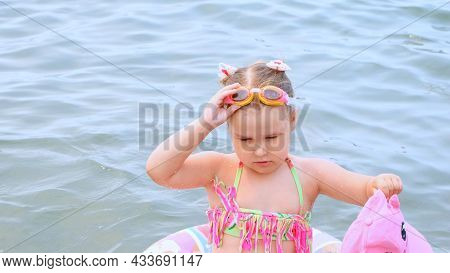Funny Little Girl 3 Years Old Swims With An Inflatable Ring, A Sun Cap And Swimming Goggles In The S