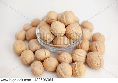 A Lot Of Whole Walnuts In A Cup On A White Background Close-up. Healthy, Organic Food With A High Co