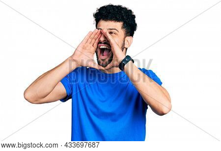 Young arab man with beard wearing casual blue t shirt shouting angry out loud with hands over mouth