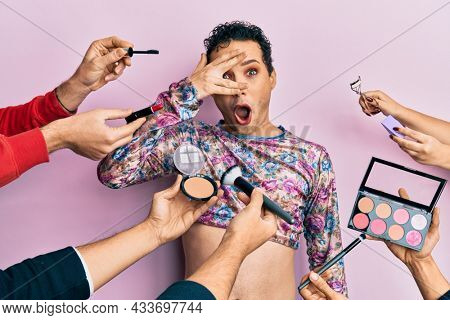 Handsome man wearing make up with make up cosmetics around peeking in shock covering face and eyes with hand, looking through fingers afraid