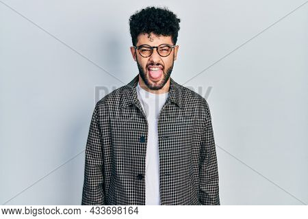 Young arab man with beard wearing glasses sticking tongue out happy with funny expression. emotion concept.
