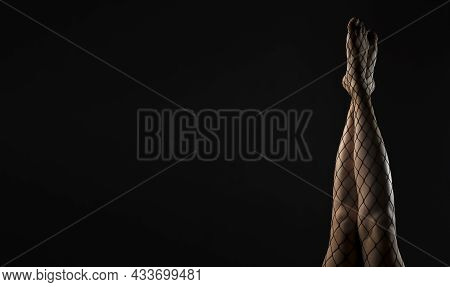 Black Fishnet Tights On Slim Legs Raised Up Over Black Background. Banner With Copy Space For Text.