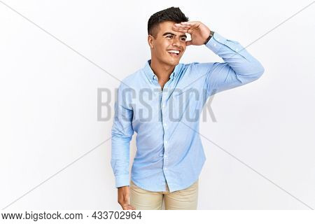 Young hispanic man wearing business shirt standing over isolated background very happy and smiling looking far away with hand over head. searching concept.