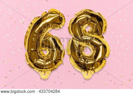 The Number Of The Balloon Made Of Golden Foil, The Number Sixty-eight On A Pink Background With Sequ