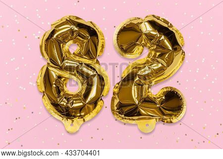 The Number Of The Balloon Made Of Golden Foil, The Number Eighty-two On A Pink Background With Sequi