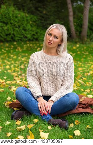 Woman Sitting Cross Legged On Green Grass. Lawn Is Covered With Yellow Autumn Leaves