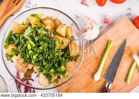 Preparing Potato Salad In A Glass Bowl - Chunks Of Potatoes With Herbs On The Table With Ingredients