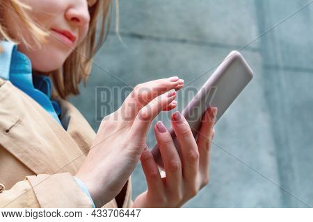 Unrecognizable Young Caucasian Woman Holding Mobile Phone In Hand. Searching Information And News. S