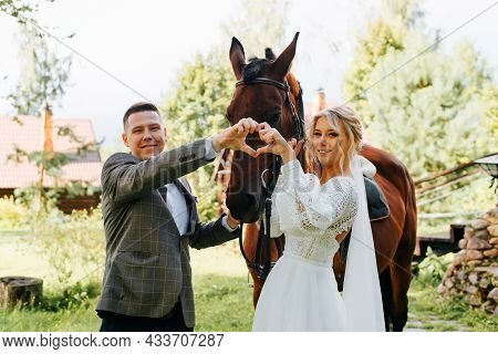 Portrait Of Happy Young Married Couple With Horse Outdoors, Smiling Newlyweds Folded Their Hands In
