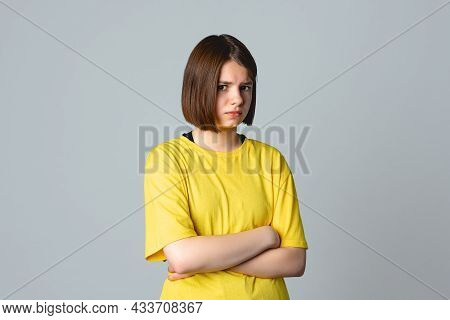 Portrait Of A Offended Teen Girl In Yellow Casual T Shirt With Crossed Arms, Standing Over Light Gre