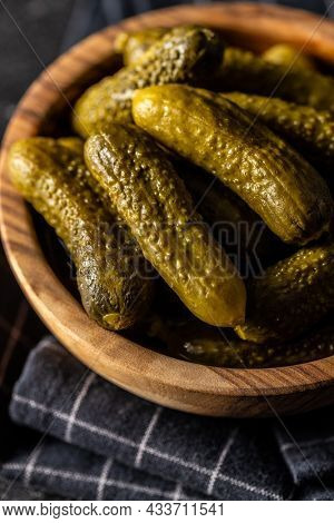 Small pickles. Marinated pickled cucumbers in wooden bowl on black table.