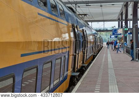 ROTTERDAM, THE NETHERLANDS - SEPTEMBER 20, 2019: Rotterdam Centraal, central station of Rotterdam with trains and platforms. The Netherlands has an efficient railway network. Passangers bording