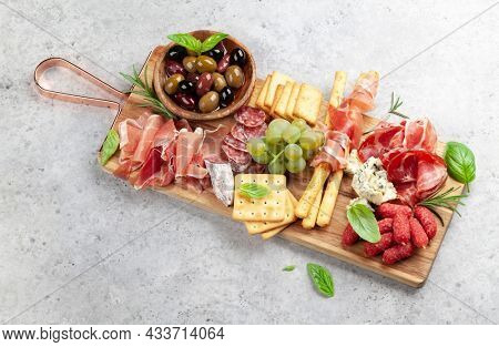 Antipasto board with prosciutto, salami, crackers, cheese and olives. Top view with copy space
