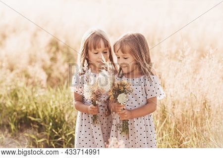 Two Little Happy Identical Twin Girls Playing Together In Nature In Summer. Girls Friendship And You