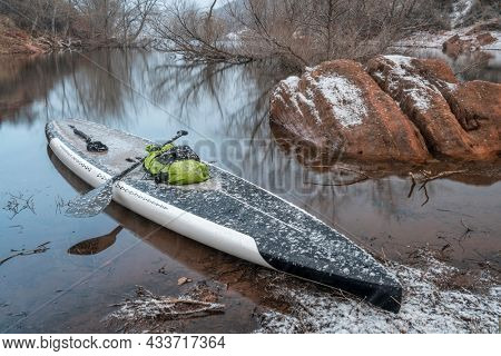 stand up paddleboard in snow blizzard on a mountain lake - Horsetooth Reservoir in northern Colorado, training, fitness and recreation concept