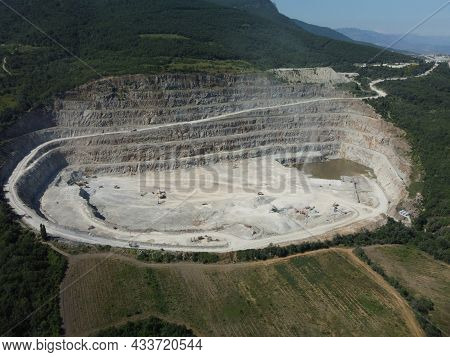 Aerial View Industrial Of Opencast Mining Quarry With Lots Of Machinery At Work - Crushed Stone And