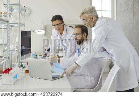 Group Of Researchers Discuss The Research With Senior Male Supervisor In The Laboratory.