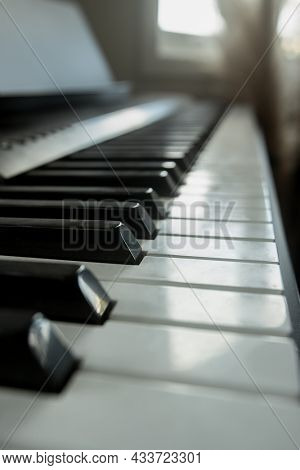 acoustic or digital piano keyboard, black and white piano keys, music equipment.