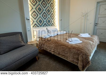 Interior Of A Spacious Hotel Bedroom With Fresh Linen On A Big Double Bed. Cozy Contemporary Room In
