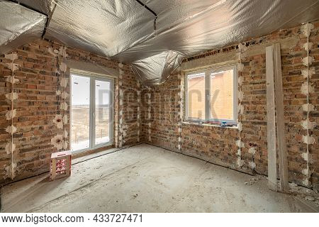 Interior Of Unfinished Brick House With Concrete Floor And Bare Walls Ready For Plastering Under Con