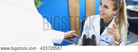 Assistant Showing Woman Chemist Information On Digital Tablet Screen In Laboratory