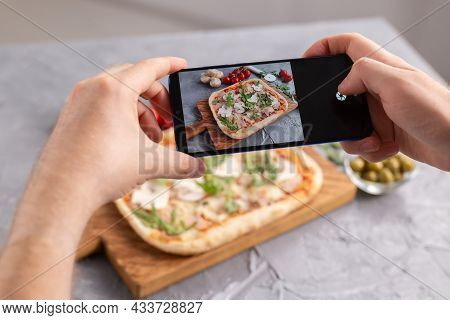 Chef Takes Pictures Of The Cooked Of Italian Pizza With Parma Ham On Smartphone. Photographing Food