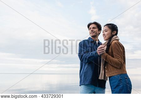 Smiling Multiethnic Couple Holding Hands Near Lake And Sky At Background