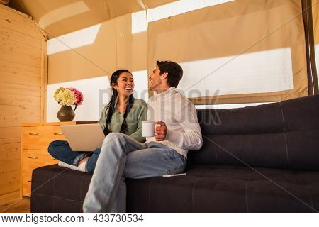 Cheerful Multiethnic Couple With Cup Using Laptop On Couch In Glamping House