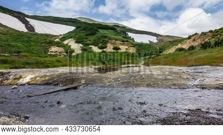 A Stream From Hot Springs Flows Along A Rocky Bed. There Are Deposits Of Sulfur On The Shore. Trickl