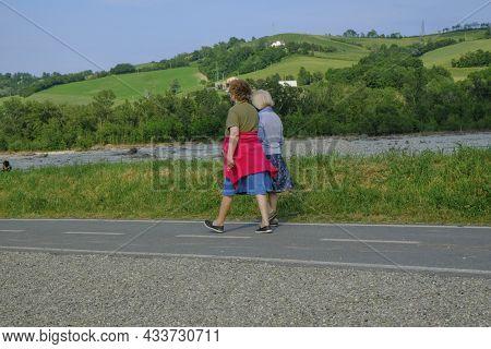Two Elder Women In Medical Masks Walking By The River And Talking. Elder Friendship. Outdoor Activit