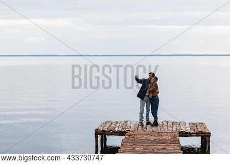 Happy Multiethnic Couple Taking Selfie On Cellphone On Pier Near Sea