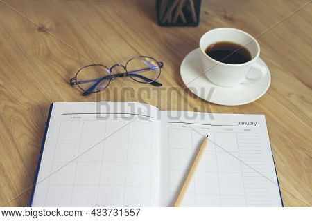 Agenda, Planner Book, Calendar, Pencil, And Cup Of Coffee Place On Office Desk. Diary For Organizer