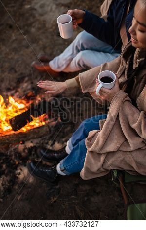 High Angle View Of Smiling Asian Woman Holding Cup Near Boyfriend And Campfire