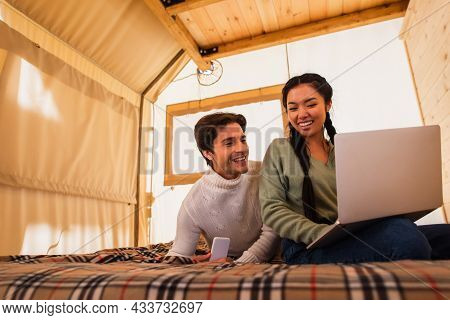 Multiethnic Couple Using Gadgets On Bed In Glamping House