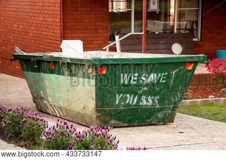 Skip Bin With Household Waste Rubbish On A Front Yard. House Clean Up Concept.