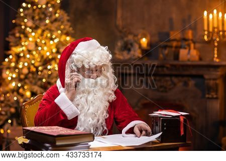 Workplace of Santa Claus. Cheerful Santa is working using smartphone while sitting at the table. Fireplace and Christmas Tree in the background. Christmas concept.
