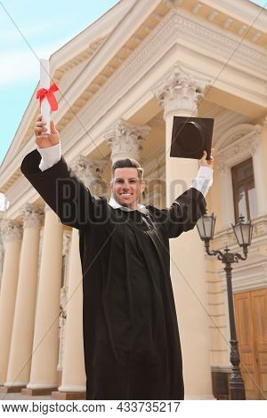 Happy Student With Diploma After Graduation Ceremony Outdoors, Low Angle View