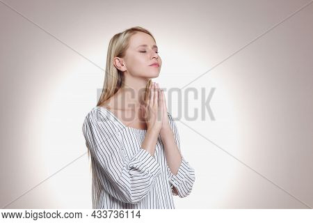 Religious Young Woman With Clasped Hands Praying Against Light Background. Space For Text