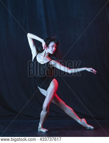 Young And Graceful Female Ballet Dancer In Motion Isolated On Dark Background In Neon Light. Art, Mo