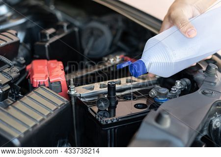 A Man Add Water To Distilled The Car Battery Maintenance And Inspections For Extended Service Life O