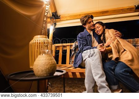 Multiethnic Couple With Blanket Holding Hands On Bench Near Glamping House