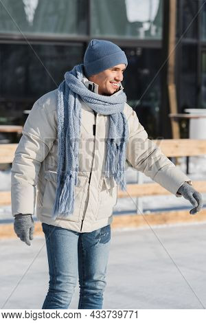 Pleased Young Man In Scarf, Winter Hat And Ice Skates Skating On Ice Rink
