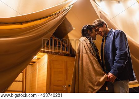 Smiling Multiethnic Couple Holding Hands Near Light Garland And Glamping House