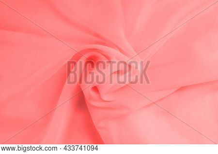 Background From Folds Of Pink Fabric Rolled Up In The Middle Close-up.