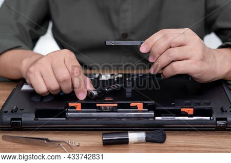 A Man Hold Hard Disk With Screwdriver In Hand Repair Laptop Computer Upgrade And Cleaning And Tool C
