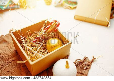Close Up Of Christmas Composition. Brown Warm Blanket And Gift Box With New Year Golden Ball, Lollip