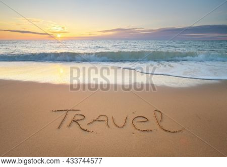 Travel word on the sea sand. Conceptual nature design.
