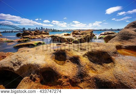 Sydney Harbour with nice rocks in the foreground the soft waves crashing on the shore and the beauti